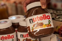 Nutella jar in hand at supermarket , Nutella is the famous italian brand of hazelnut chocolate spread. Mulhouse - France - 15 September 2018 - closeup of Nutella royalty free stock photo