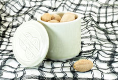 Nutmeg. In ceramic container with cloth background Stock Image