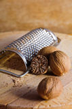 Nutmeg. And grater on a wooden background royalty free stock photo