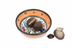 Nutmeg in ceramic bowl Royalty Free Stock Images