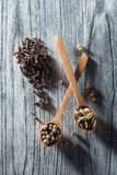 Nutmeg, clove and allspice in old spoon on wood Stock Photo