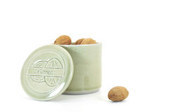 Nutmeg in container. Nutmeg in ceramic container isolated on white Stock Images