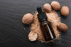 Nutmeg essential oil on a dark stone background.  royalty free stock photo