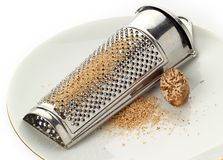 Nutmeg and grater. On a plate, with freshly ground spice royalty free stock photo