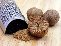 Nutmeg with grater. Selection of nutmeg with grater on a wooden background royalty free stock images