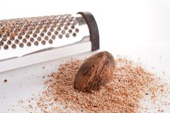 Nutmeg and Grater. Fresh ground nutmeg with a whole seed grater Royalty Free Stock Images