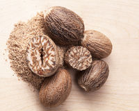 Nutmeg ,  half and ground on on wooden plank Royalty Free Stock Photo