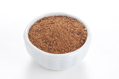 Nutmeg powder in a bowl on white background. Stock Photo