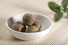 Nutmeg in white china bowl. Nutmeg in small bowl on placemat decorated with leaves royalty free stock image