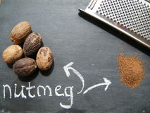 Nutmeg. Whole nutmeg, grater and grated nutmeg on a black background Royalty Free Stock Photography