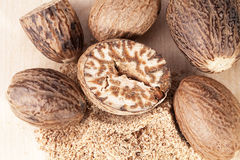 Nutmeg , whole, half and ground on wooden plank Royalty Free Stock Photo
