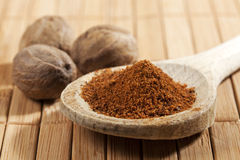 Nutmeg. Whole nuts behind wooden spoon with a heap of powder royalty free stock image