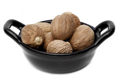 Nutmegs. Whole nutmegs in small black dish, isolated on white Stock Photo