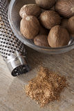Nutmegs in a bowl. Some whole nutmeg in a glass bowl next to a nutmeg grater and grated nutmeg Stock Photography