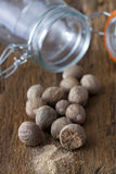 Nutmegs before an empty glass Royalty Free Stock Photography
