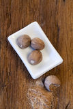 Nutmegs in porcelain bowl Stock Photo