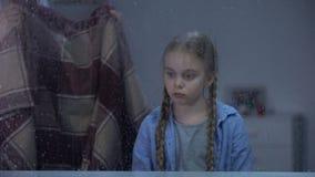 Nutra a coberta de pouca criança com a cobertura no dia chuvoso frio, criança doente no hospital filme