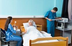 Nutra e medique testes de condução em um paciente em uma cama de hospital Imagens de Stock