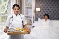 Nutra guardar a bandeja do café da manhã quando paciente que encontra-se na cama em casa imagem de stock royalty free