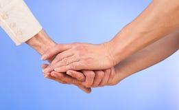 Nutra lovingly guardar a mão de uma mulher idosa fotos de stock