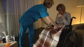 Nutra a mulher adulta da coberta na cadeira de roda com cobertura, auxílio e ajuda vídeos de arquivo