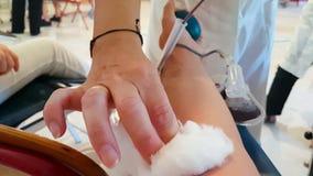Nutra remover a agulha de uma mão do ` s do homem que se ofereça como um doador de sangue vídeos de arquivo