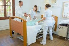 Nutre o paciente de levantamento sob a supervisão do ` s do doutor fotos de stock