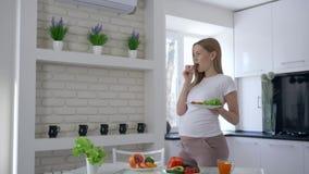 Nutrição saudável, mãe futura com a placa da salada em suas mãos comendo um pepino e carícias sua barriga no video estoque