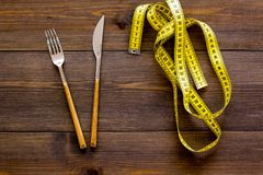 Nutrición apropiada para adelgazar Bifurcación, cuchillo y cinta métrica en la opinión superior del fondo de madera oscuro foto de archivo libre de regalías