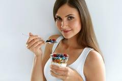 Nutrición de la dieta sana Mujer que come el yogur, bayas y el cereal foto de archivo