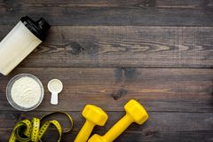 Nutrición para el crecimiento del músculo Cucharada de la proteína cerca de la coctelera, pesa de gimnasia, cinta métrica en la o imágenes de archivo libres de regalías