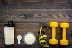 Nutrición para el crecimiento del músculo Cucharada de la proteína cerca de la coctelera, pesa de gimnasia, cinta métrica en la o fotos de archivo