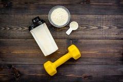 Nutrición para el crecimiento del músculo Cucharada de la proteína cerca de la coctelera, pesa de gimnasia en la opinión superior foto de archivo libre de regalías