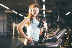 Nutrición y ejercicio de los deportes la mujer hermosa sostiene la proteína en su mano en botellas, coctelera, escucha música en  fotos de archivo libres de regalías