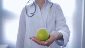 Nutricionista com a maçã verde em estiramentos das mãos na câmera que recomenda a dieta saudável para o bem-estar, unfocused filme