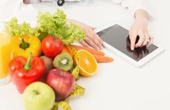 Nutricionista de sexo femenino que trabaja en la tableta digital fotos de archivo