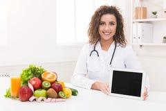 Nutricionista del doctor que sostiene la tableta digital en blanco, maqueta imagen de archivo libre de regalías