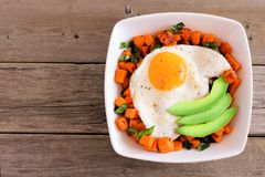 Nutrient bowl with sweet potato, egg, avocado and spinach over rustic wood Royalty Free Stock Image