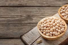 Nutrient-dense food - raw chickpeas grains in bowl on a wooden rustic table stock image