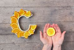 Nutriente da vitamina C no conceito do alimento Placa na forma da letra C com fatias alaranjadas e da mão da mulher com o citrino imagem de stock royalty free