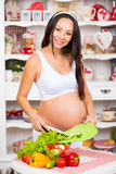 Nutrição e gravidez saudáveis A mulher gravida de sorriso nova corta vegetais na salada Fotografia de Stock Royalty Free