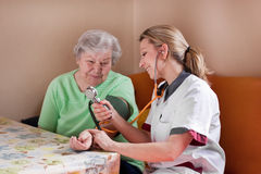 Nutrisca la pressione sanguigna di misure di una donna anziana Immagini Stock