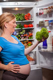 Nutrition And Diet During Pregnancy. Pregnant Woman Standing Near Refrigerator With Fruits And Vegetables Royalty Free Stock Photos