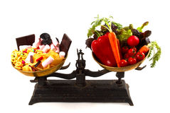 Nutrition balance. Healthcare concept: the choice between healthy and unhealty on scales Stock Photo