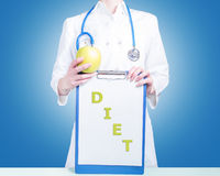 Nutrition. Clipboard with the words: Diet and Woman doctor with a green apple Royalty Free Stock Images