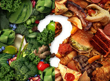 Nutrition Confusion Idea. And diet decision concept and food choices dilemma between healthy good fresh fruit and vegetables or greasy cholesterol rich fast Royalty Free Stock Photo