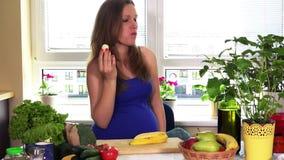 Nutrition de temps de grossesse La femme enceinte mangent la banane se reposant près de la table de cuisine clips vidéos