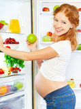 Nutrition and diet during pregnancy. Pregnant woman with fruits. Nutrition and diet during pregnancy. Pregnant woman standing near refrigerator with fruits and Royalty Free Stock Photography