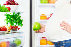 Nutrition and diet during pregnancy. Pregnant woman with fruits. Nutrition and diet during pregnancy. Pregnant woman standing near refrigerator with fruits and stock photo