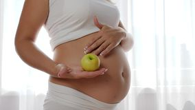 Nutrition and diet during pregnancy, woman with baby in belly keeps in hand green apple. Close-up stock video